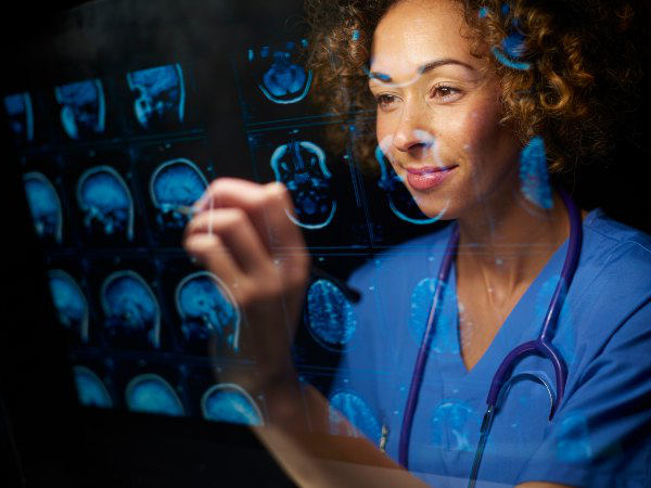 A health professional wearing scrubs examines digital images of brains