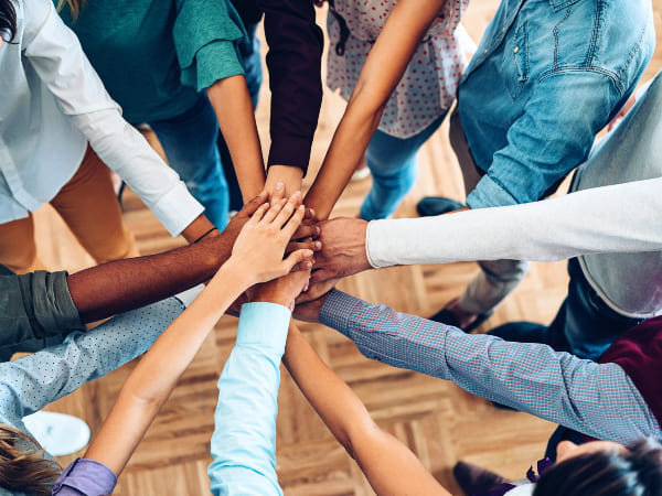 A group of diverse people standing in a circle with hands in the middle