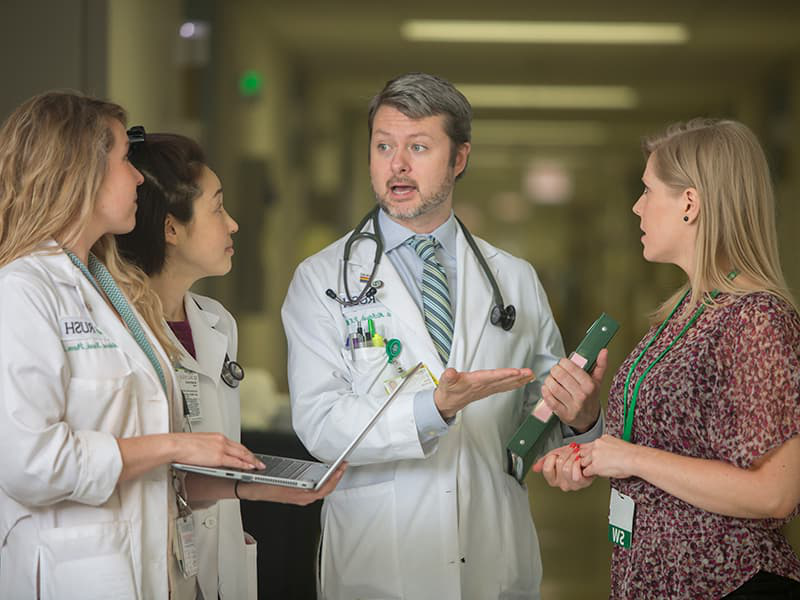 A Rush nurse practitioner meets with his colleagues