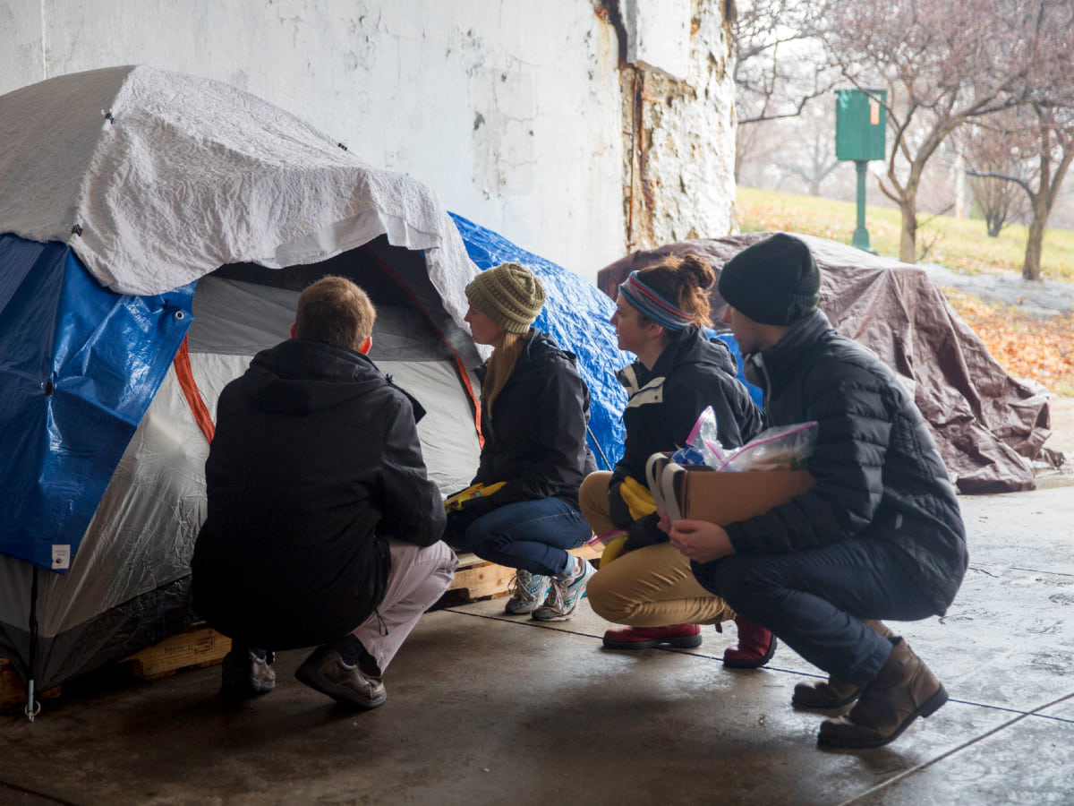 Rush students squat beside a tent under a viaduct