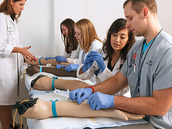 Medical students practice injections using prosthetic arms